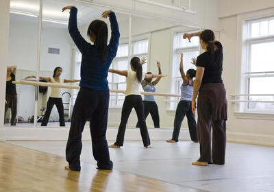Group of students rehearses facing a dance barre and mirror