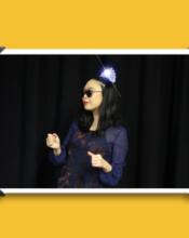 Jisu, wearing sunglasses and a tiara, dances awkwardly.